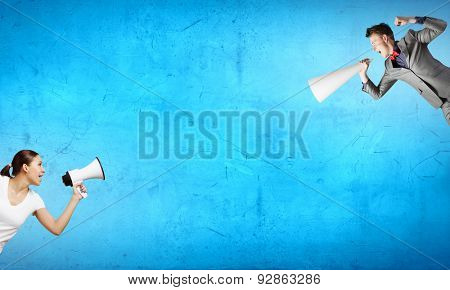 Two business people shouting in megaphones at each other