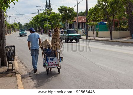 Carbage Collector Walking On A Street In Cuba
