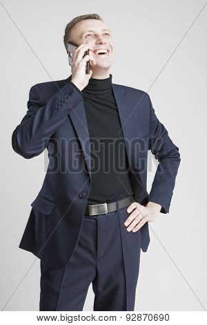 Epressive Handsome Caucasian Man In Elegant Siut Speaking By Cell Phone And Smiling. Against White