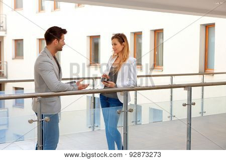 Business partners talking in corridor of apartment house.
