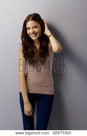 Happy young woman posing by grey wall, hand in hair.