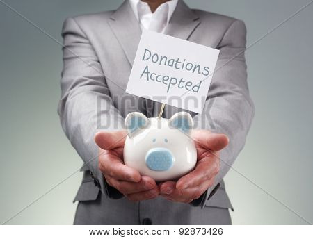 Businessman holding piggy bank donation box for charity fundraising, investment or venture capitalist loan