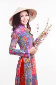 Beautiful Vietnamese woman with tradition ao dai with modern design and palm-leaf conical hat ( non la ) on white background poster