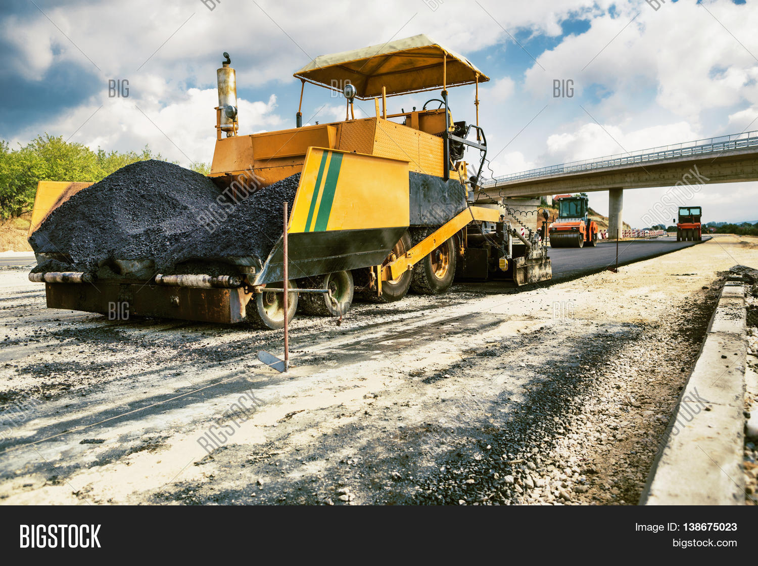 new road pavement machine laying fresh asphalt or bitumen on top of the gravel base