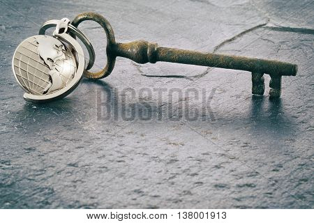 Keychain figure of world and old key secrets on stone table