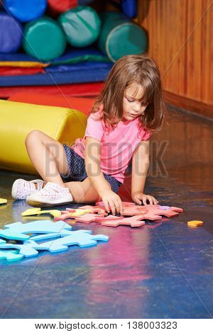 Girl solving a big jigsaw puzzle on the floor in a kindergarten