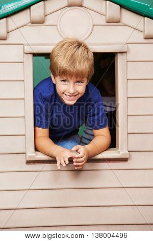 Smiling boy looking through window in a playhouse in kindergarten