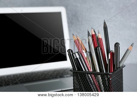 Pencils and pens in metal holder with laptop, close up