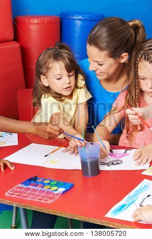 Children painting images in child care after elementary school with teacher
