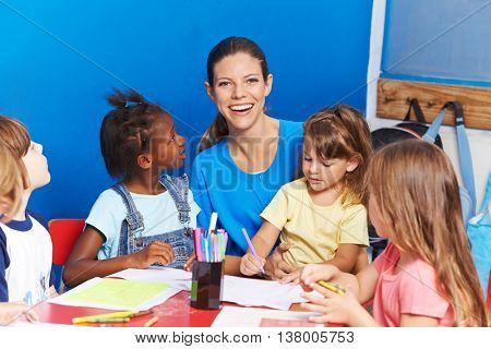 Happy nursery teacher with children painting in a kindergarten