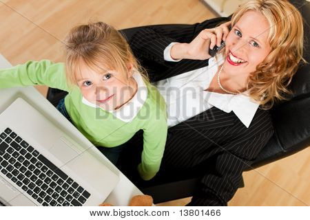 Family Business - telecommuter Businesswoman and mother with kid on her lap is making a phone call, both are looking to the viewer