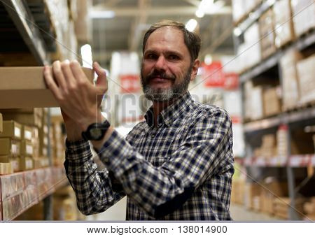 Mature man picking up a pack from the rack in a store