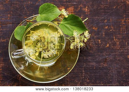 Glass cup of linden tea with fresh flowers on dark wooden baskground. Top view.