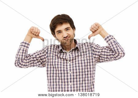 Close-up portrait of handsome funny young blue-eyed dark-haired man wearing casual plaid shirt showing muscles and pointing backward with his thumbs looking at camera. Isolated on white background.