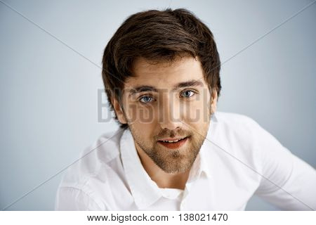 Close up portrait of elegant smiling handsome young businessman in white shirt looking at camera. Studio, isolated on grey background.