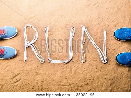 Blue running shoes and run sign made of shoelaces against sand background, studio shot, flat lay