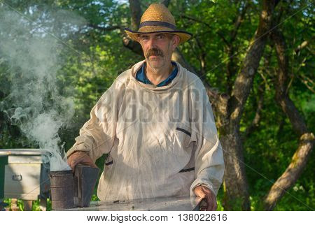 Portrait of Ukrainian bee-keeper at work place