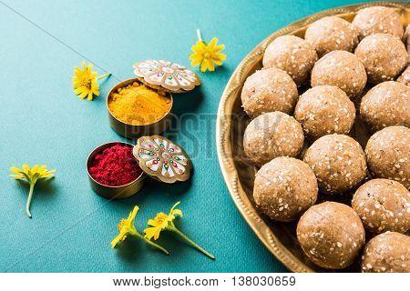 sesame laddu or tulgul or til gul laddu or ladu served in brass plate, favourite sweet dish in Makar Sankranti Festival in India, indian festival sweets, huldi kumkum with flowers, kite festival