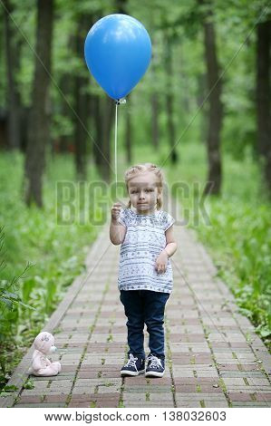 Little girl with blue balloon and teddy bear