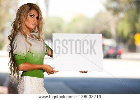 Transgender person holding blank sign street side for advocation phrases.
