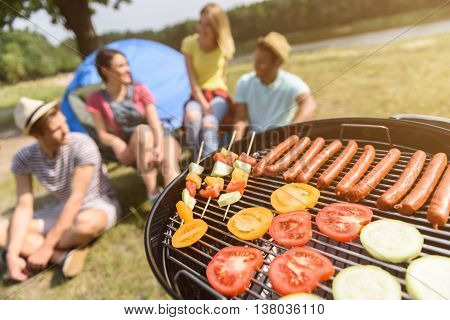Cheerful men and women relaxing in the nature. They are sitting and smiling. Focus on grill with roast meat and vegetables