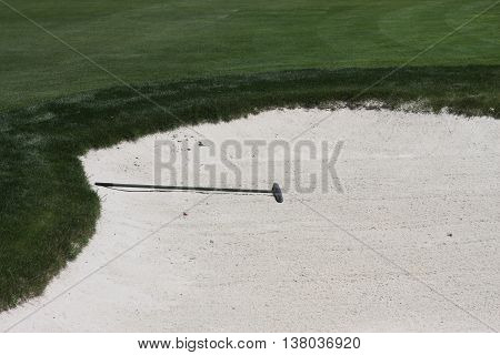 This is an image of a golf course sand trap and rake taken in full sun.