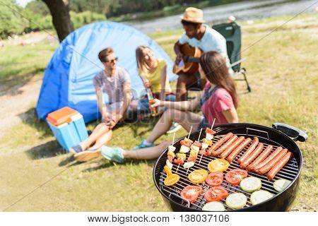 Young men and women are singing to guitar in forest. They are sitting and smiling. Focus on roast sausages and vegetables on grill