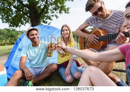 Cheers. Carefree men and women are clinking bottles of beer. They are sitting near tent and laughing. Young guy is playing guitar and singing