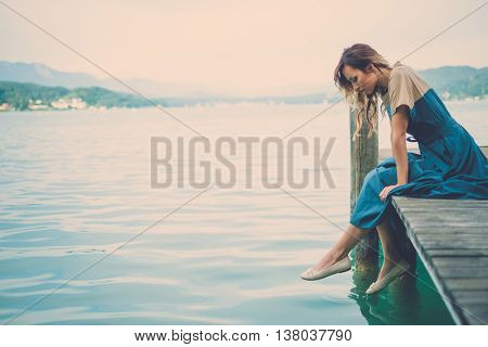 Well-dressed woman sitting on a wooden pier with mountain lake view.