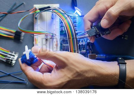 Robotics development closeup., electronic invention. Engineer, programmer, inventor hands with special cables, wires, working with breadboard and constructing robot at home. Modern technologies. Hobby