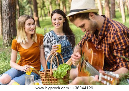 Handsome young man is playing guitar with inspiration. Girls are listening with admiration and smiling. They are sitting on grass in forest