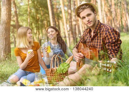 Happy friends are making picnic in nature. They are sitting on blanket and laughing. Man is playing guitar for women