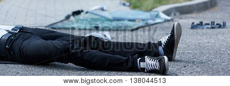 Man lying on the street after car accident poster