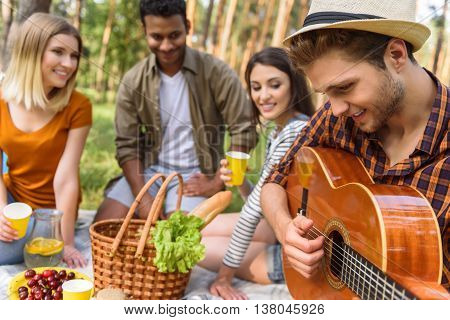 Shy young man is playing guitar and smiling. His friends are sitting and listening to music with pleasure. They are relaxing in forest