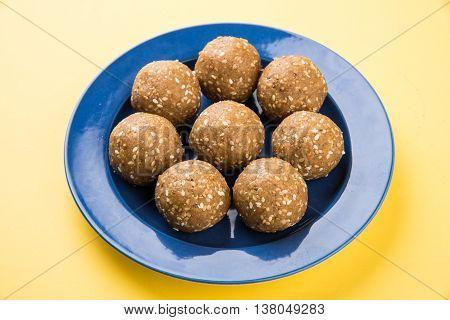 sesame laddu or tulgul or til gul laddu or ladu, favourite sweet dish in Makar Sankranti Festival in India, 14 january, indian festival sweets, served in triangle plate