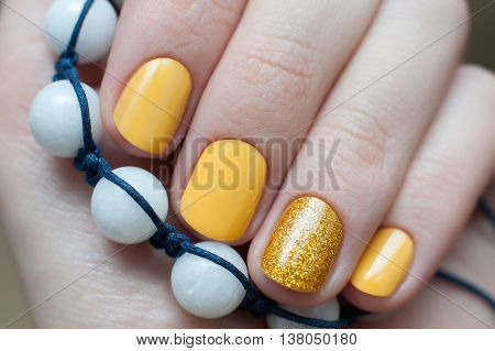 Beautiful female hand with yellow nail design. Close up.