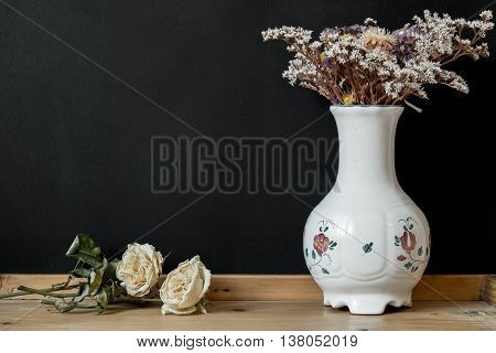 White Hungarian Herend porcelain vase with dry flowers on black background with copy space