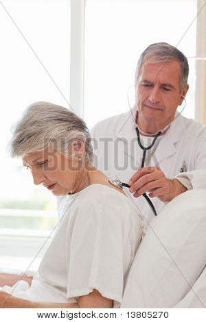 Senior doctor taking the heartbeat of his patient