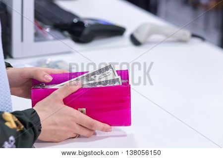 Money in wallet, woman gives money to seller