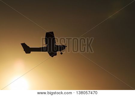 The plane flies against the backdrop of sunrise, air tourism