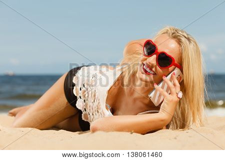 Young girl lying on beach with sunglasses talking using cellular phone. Communication and internet concept.