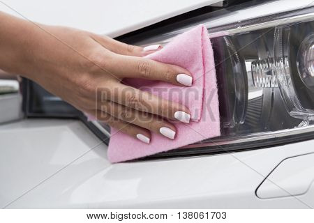 Woman's hand with a cloth to clean the headlights of the car