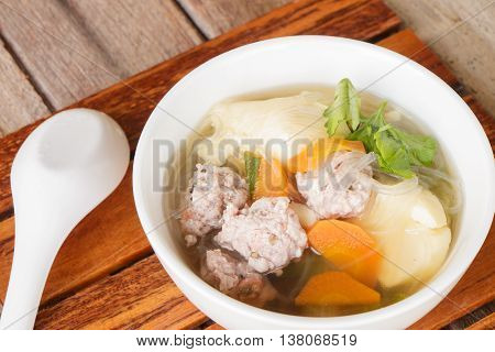 clear soup with pork in white plate put on wooden background, Thai cuisine.