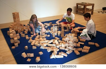 LONDON,UK - JULY 06, 2016: Visitors use wooden bricks to create interactive art piece in New Tate Modern Building, London