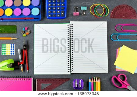 Opened Blank Lined School Notebook With Frame Of School Supplies Over A Chalkboard Background