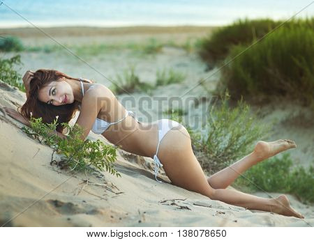 beautiful woman in a bathing suit lying on the sand by the sea shore