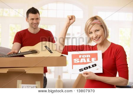 Smiling woman holding sold sign raising fist, happy man looking at her in background, unpacking boxes.?