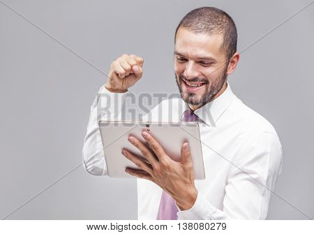 Excited business man holding a tablet computer on grey background