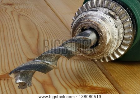 Electric drill on a wooden background closeup