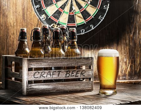 Crafting beer in bottles and glasses. On a wooden wall hangs game of darts.